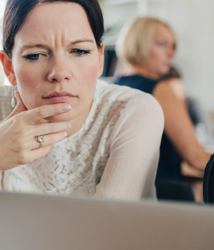 Confused Businesswoman Looking At Laptop While Sitting At Desk