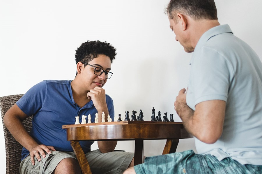 Men Of Three Generations During A Game Of Chess